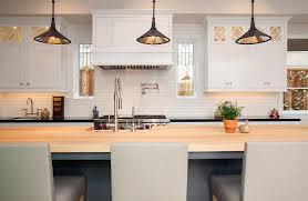 gray kitchen island with maple countertops and light gray leather counter stools