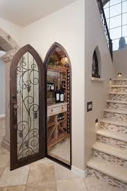 climate controlled wine cellar built in under stair storage closet with foam insulation iron entry door and interior design features and chandelier in
