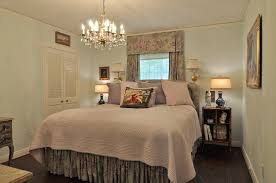 narrow master bedroom ideas with crystal chandelier and dark wood flooring design