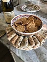 completed wine cork wreath or trivet displayed on a counter with a bowl of s in