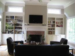 black flat screen tv on white painted wall over exposed brick fireplace combined with white wooden