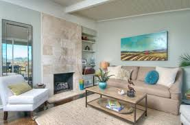 light blue walls tile fireplace column white armchair beige sofa beige rug wooden coffee table landscape