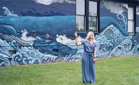 a blonde woman standing in from of the nashville mural in germantown alexis and bolt