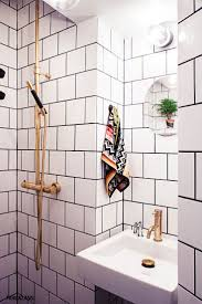 bathroom white tiles: a great design and fantastic use of a small space we love the contrast of the grout and tile with brass hardware