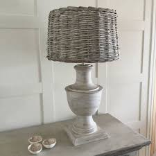 delicate pale white wash wooden lamp and wicker shade