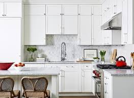 wicker stools seated at a white kitchen island with gray marble countertops matching perimeter countertops and gray mini marble backsplash tiles