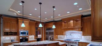 ambiance is abound in this gorgeous kitchen with recessed lighting in the ceiling and hanging pendant lights over the island