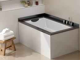 japanese soaking tub with seat. the yasahiro japanese style soaking tub, used as a corner bath. shown undermounted witha tub with seat