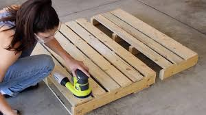 sanding a diy dog bed made from a wooden pallet