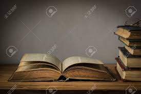 old book open on a wooden table with gles stock photo 41199505