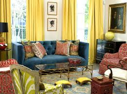 yellow and blue living room design with bright yellow silk drapes blue velvet tufted sofa glossy black vintage dresser chest brass cocktail table bright yellow sofa living