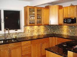 oak cabinets with black countertops granite