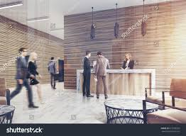 suits office. People In Business Suits Are Walking Past A Ligth Wood Reception Counter Standing An Office