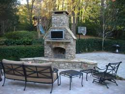outdoor daybed set near the corner outdoor fireplace with tv above