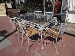 classic style wrought iron patio furniture including rectangular glass top table and wood seat chairs