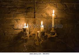 Candles burning in old candleholder fixed to wall - Stock Image