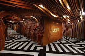 inside lighting. Inside The Entrance Of This Nightclub, Wooden Panels With Organic Curves And Hidden Lighting Guide