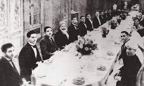 allama iqbal centre right in his characteristic headgear sitting alongside quaid i