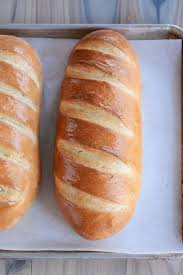 two loaves of fresh homemade french bread on a parchment lined sheet pan