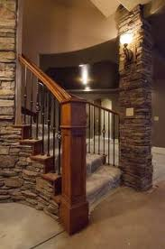 basement stairwell lighting. stacked stone newels iron balusters and the torch style sconce lighting is a whimsical dungeony touch for basement stairwell r