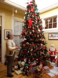 Beryl Baker stands next to a 12-foot-Christmas tree, which is one