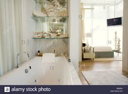Luxury hotel bathroom with large bathtub, bedroom in background - Stock  Image