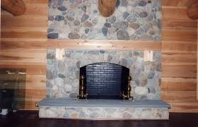 This field stone fireplace has a concrete hearth and cedar mantle.