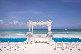beach wedding chairs. Beach Wedding Setup With Blue-covered White Chairs And Arch Decorated Sand Dollars