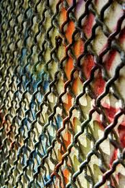 a chain link fence against a wall with colourful spray painted graffiti barcelona spain