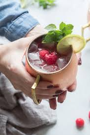 close up of hands holding raspberry moscow mule with mint leaves lime wheel and raspberries