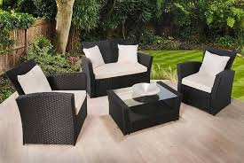a rattan sofa armchairs and table on decking
