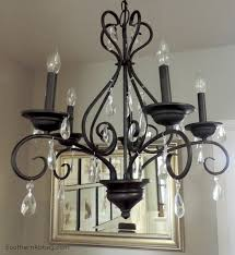 impressive black iron hanging ornate chandelier complete with small fluorescent light