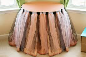 with a piece of elastic to hug the table top or add a hook and loop fastener to the table skirt to make sure it stays in place all through the event