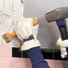 chiseling tile off a wall in preparation for new tile installation if you re