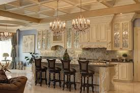 crystal chandeliers with coffered ceiling and white kitchen