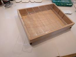 light wooden box sits atop white paper at a slight angle filling the upper two thirds