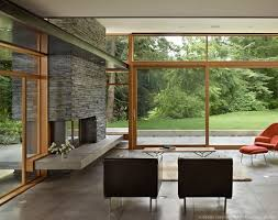 Fireplace and glass walls. via Mid-Century modern home with a nature  backdrop on