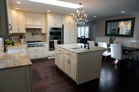 cream color cabinet kitchen with island chandelier and dining table