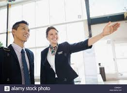 Airport Customer Service Representative Guiding Businessman Stock