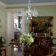 A Green Dining Room With Ghost Chandelier And Round Table