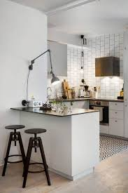 a small white kitchen island with a black countertop and black industrial stools for having breakfasts