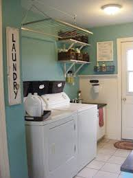 simple and clean basement laundry room after remodel with light blue painted wall decor combined with white furniture plus wall mounted detergent storage