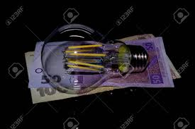 Light Bulb On Money On A Black Background Stock Photo Picture And