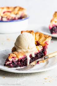 a piece of blackberry pie with a scoop of ice cream on a plate