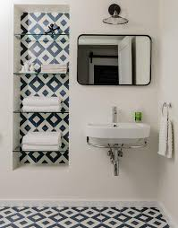 blue and white bathroom with diamond pattern tiles in a bathroom decorating the background of inset shelveatching floors