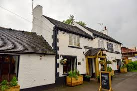 the plough is a white painted roadside pub that presumably was there long before the suburban housing that now surrounds it inside there s a narrow area