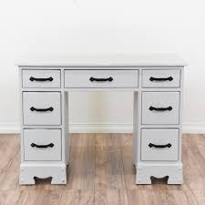 This kneehole desk is featured in a solid wood with a fresh white coat of  paint