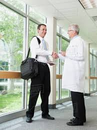 Pharmaceutical Representative Doctor Talking With Pharmaceutical Representative In Hospital