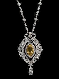 estate yellow sapphire and diamond pendant brooch on a diamond and platinum chain