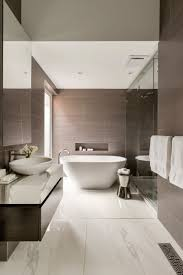 The large tiles featured on the walls of this bathroom bring out the darker  flecks found in the tiles used for the floors.